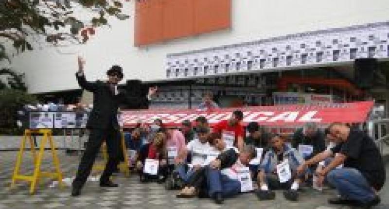 Bancários paralisam agências do Itaú com caixão, remédios e crachás no Guarujá